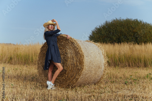 Beautiful girl villager posing in a dress near a bale of hay in a field Fototapeta