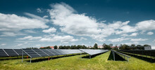Solar Power Plant, Blue Solar Panels On Orange Autumn Grass Field Under Blue Sky With Clouds. Toned Panoramic Image. Solar Power Generation, Renewable Energy Production