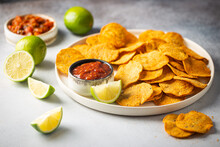 Single Big White Plate Of Yellow Corn Tortilla Nachos Chips With Salsa Sauce Over White Table
