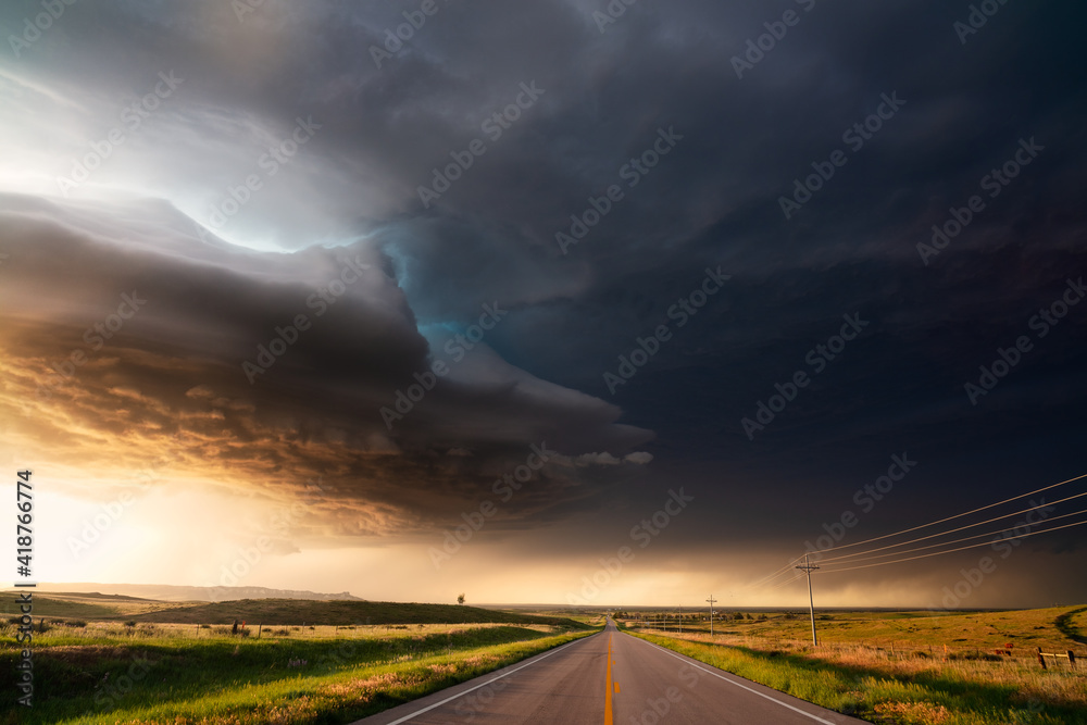 Fototapeta Supercell storm with dramatic clouds over a road at sunset