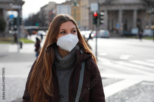 Young woman walking in city street wearing KN95 FFP2 face mask protective. Copy space. - fototapety na wymiar