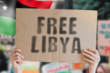 """The Phrase """" Free Libya """" On A Banner In Men's Hand With Blurred Libyan Flag On The Background. Protest. Riot. Violence. Economic Crisis. Collapse. Politics. Streets. Save. Cruelty"""