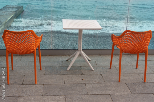 Canvas Print A table and two chairs stand on the embankment in a street cafe.