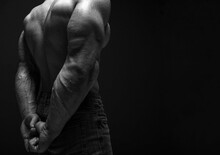 Pumped Up Strong Sweaty Upper Body Back And Biceps Of Brutal Man Athlete In Jeans Standing Showing Perfect Shape Over Dark Background. Sport Men Body Concept