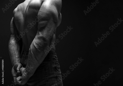 Fotografering Pumped up strong sweaty upper body back and biceps of brutal man athlete in jeans standing showing perfect shape over dark background