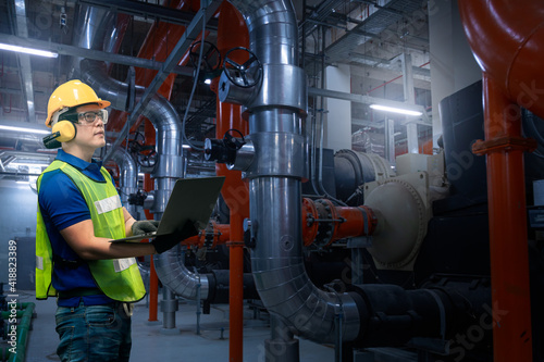 Fototapeta Engineer under checking the industry cooling tower air conditioner is water cooling tower air chiller HVAC of large industrial building to control air system