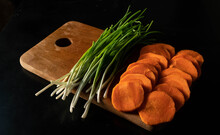 Vegetables On The Board Onion And Carrot Black Background