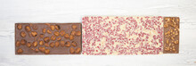 Different Sweet, Delicate Chocolate Bars Lie Creatively On A White Wooden Background