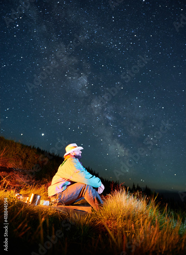 Fényképezés Side view of adult man which sitting on the mountain hill and enjoying scene of night stars