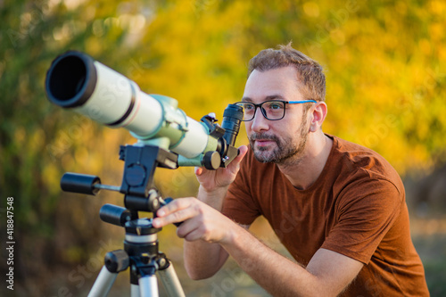 Canvas Amateur astronomer looking at the sky with a telescope.