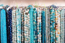 Multicolored Beads Made Of Gems Strung On Thread Displayed On Stand In Store Of Jewelry Accessories