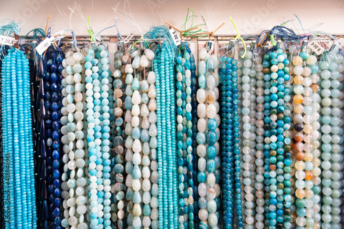 Slika na platnu Multicolored beads made of gems strung on thread displayed on stand in store of