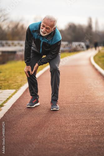 Wallpaper Mural Active senior man is having pain in knee while jogging.