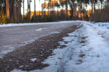 Coniferous Forest. Dirty Spring Gravel Road With Snow Ice And Puddles In Golden Evening Sunset