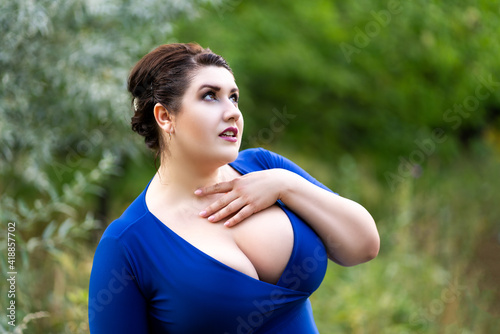 Sexy plus size model in blue dress with a deep neckline outdoors, beautiful fat woman with big breasts in nature - fototapety na wymiar