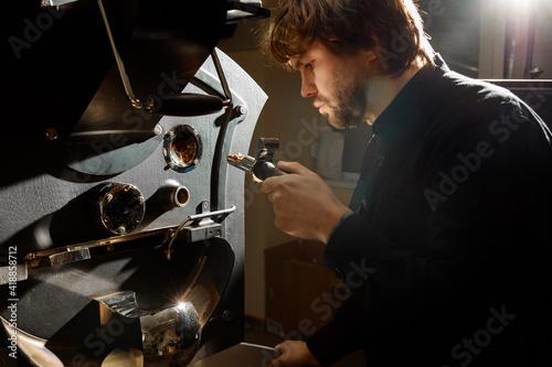 Fotografija confident coffee roaster man is checking preparation process