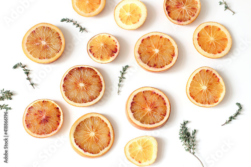 Canvas Close-up of fresh whole and slice cut bloody oranges with thyme herb isolated on white table backgrounds