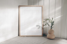 Portrait Empty Wooden Frame Mockup In Sunlight. Olive Branch In Modern Organic Shaped Vase. Beige Linen Table Cloth. White Wainscot Wall Paneling Background. Scandinavian Interior, Home Design. Art