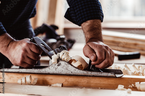 Carpenter's hands planing a plank of wood with a hand plane Fotobehang