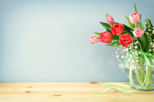Spring Bouquet Of Red And Pink Tulips Flowers In The Glass Vase Over Wooden Table