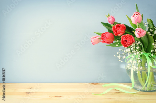 spring bouquet of red and pink tulips flowers in the glass vase over wooden tabl Wallpaper Mural