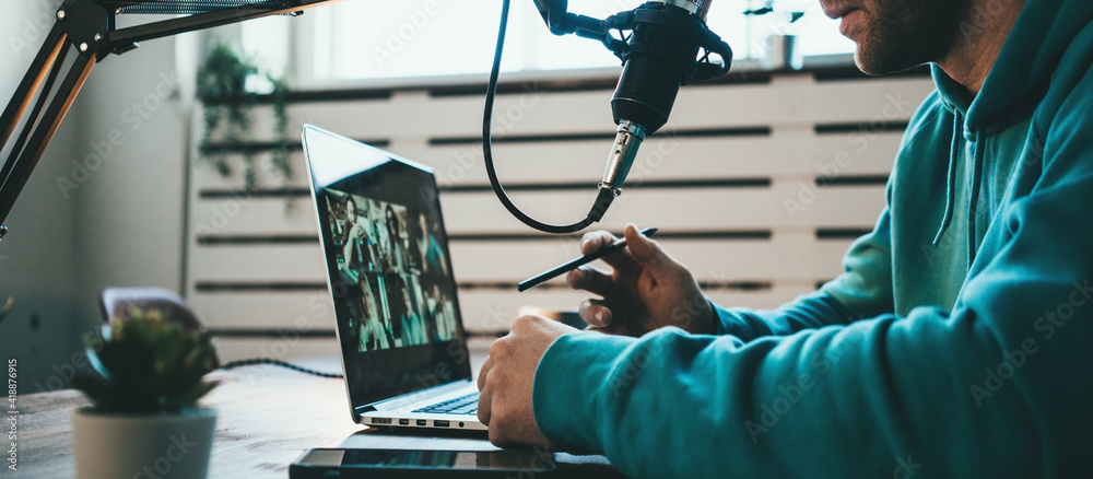 Fototapeta Host streaming his live podcast using professional microphone at his simple broadcast studio