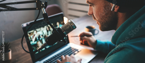 Fotografia Handsome host streaming his audio podcast using microphone and laptop at his hom