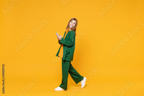 Obraz Full length side profile view of little blonde smiling kid girl 12-13 years old wearing casual clothes hold mobile cell phone walk isolated on yellow background children Childhood lifestyle concept. - fototapety do salonu