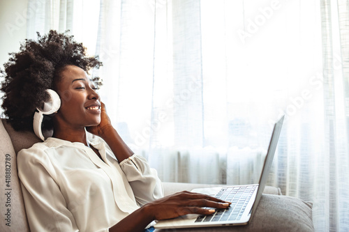 Fotomural Shot of a young woman using headphones while relaxing on the sofa at home