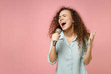 Young Black African American Expressive Fun Curly Singer Woman 20s Wearing Blue Casual Shirt Singing Song In Microphone Enjoy Karaoke Club Isolated On Pastel Pink Color Background Studio Portrait.