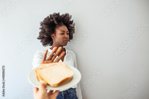 Fotografia, Obraz Young woman on gluten free diet is saying no thanks to toast