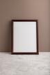 Brown wooden frame mockup on beige paper background. Blank, vertical orientation, still life.