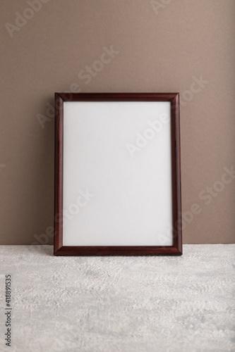 Fototapeta Brown wooden frame mockup on beige paper background. Blank, vertical orientation, still life. obraz