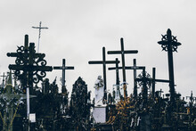 Statue Of Virgin Mary Holding Baby Jesus In Her Hands Amongst Giant Wooden Crosses. Spooky Spiritual Concept.