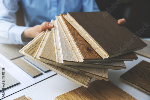 Obraz parquet floor - store salesman with flooring samples in hands - fototapety do salonu