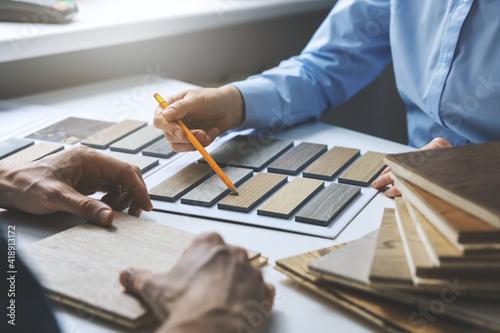 Obraz interior designer and customer choosing furniture and flooring materials from samples at design shop - fototapety do salonu