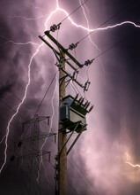 Bright Lightning Bolts Striking Electric Power Pylon Tower Cables And Sub Station Strike. Electricity Discharge Cloud To Ground Storm With Transformer On Wooden Telegraph Pole Silhouette Against Sky