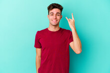 Young Caucasian Man Isolated On Blue Background Showing Rock Gesture With Fingers
