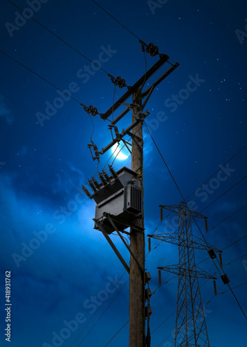 Electric power pylon cables at night blue hour moon sky shining. High voltage electricity substation on wooden pole tower silhouette against Mother Nature moody bright evening sky.