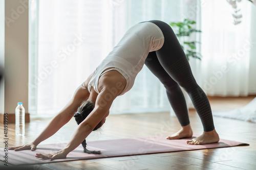 Beautiful Attractive Asian woman practice yoga Downward Facing dog or yoga Adho Fototapeta