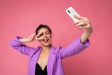 Smiling Sexy Woman Wearing Purple Suit Taking Selfie Photo On The Mobile Showing Tongue And Peace Gesture Phone Isolated Over Pink Background Looking At Cell Display