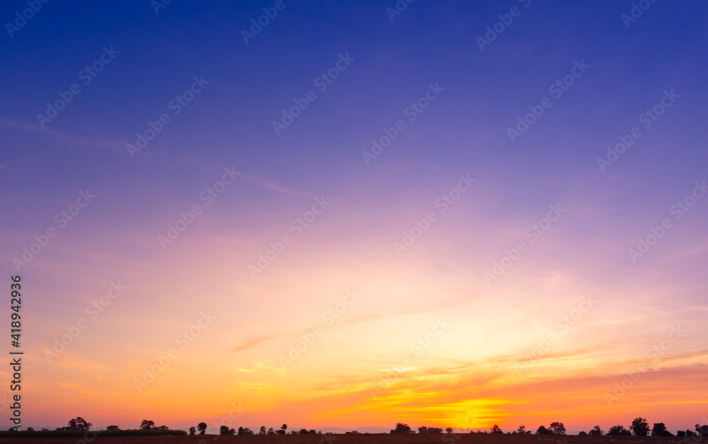 Fototapeta Beautiful Vivid sky painted by the sun leaving bright golden shades.Dense clouds in twilight sky in winter evening.Image of cloud sky on evening time.Evening Vivid sky with clouds.