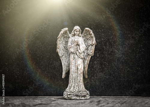Canvas-taulu Small old weathered stone weeping angel with wings ornament standing in sorrow o