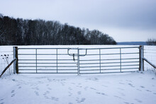 Closed Gate To Snowy Field With Dark Clouds Overhead In UK