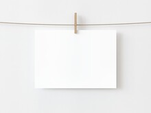One Blank Horizontal Rectangle Note Paper Card Hanging With Wooden Clip Or Clothespin On Rope String Peg Isolated On White Backgroun. 3D Illustration