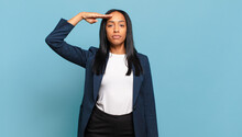 Young Black Woman Greeting The Camera With A Military Salute In An Act Of Honor And Patriotism, Showing Respect. Business Concept