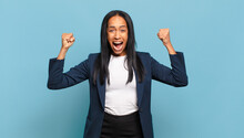 Young Black Woman Shouting Aggressively With An Angry Expression Or With Fists Clenched Celebrating Success. Business Concept