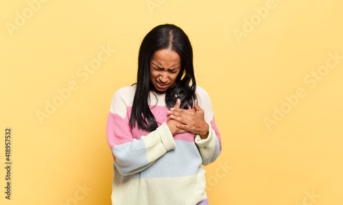 Canvas Print young black woman looking sad, hurt and heartbroken, holding both hands close to