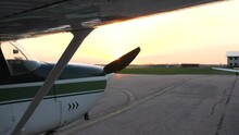 Slider Shot Of Small Aircraft Parked On A Ramp Before Takeoff, Sun Setting