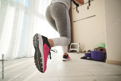 A woman performs lunges during functional training with fitness straps Wallpaper Mural